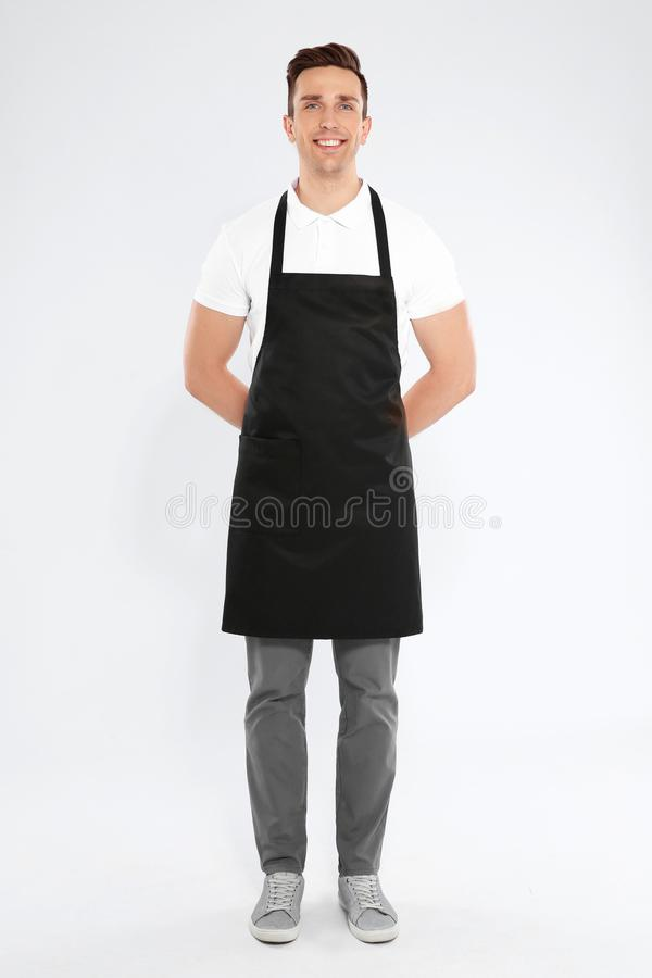 Full length portrait of handsome waiter in apron stock images