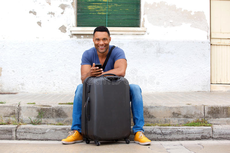 Full length handsome young african man sitting with suitcase and smart phone. Full length portrait of handsome young african man sitting by the road with stock photo