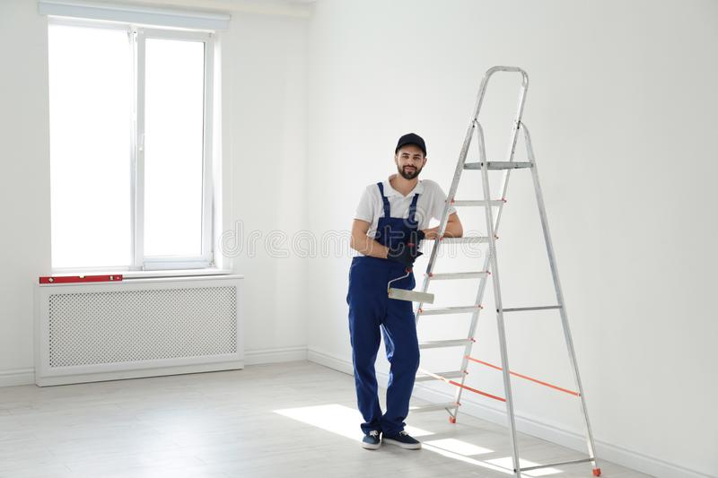 Full length portrait of handyman with roller brush near ladder indoors. Professional construction tools. Full length portrait of handyman with roller brush near royalty free stock photos