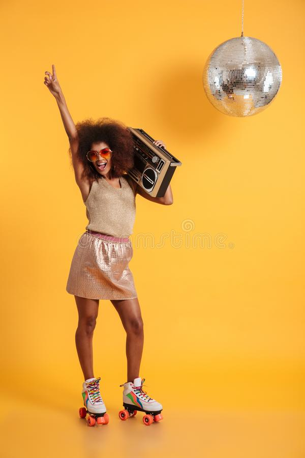 Full length portrait of happy afro american disco woman in sunglasses pointing with finger upward, standing on roller stock photography
