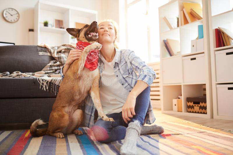 Woman with Shepherd Dog. Full length portrait of happy Asian woman posing with shepherd dog at home in sunlight, copy space stock photo