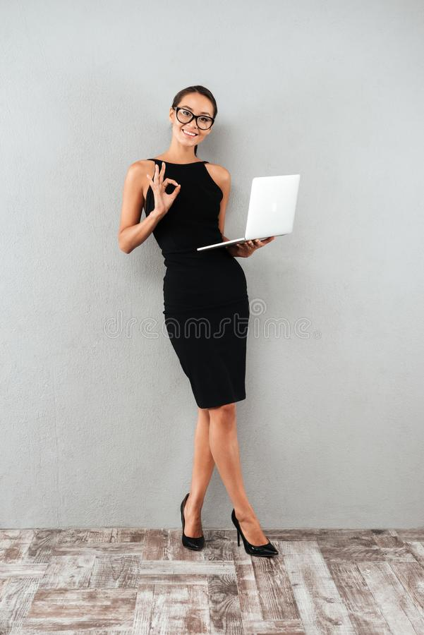 Full length portrait of a happy attractive businesswoman. In black dress and eyeglasses holding laptop computer and showing ok gesture while standing isolated stock images
