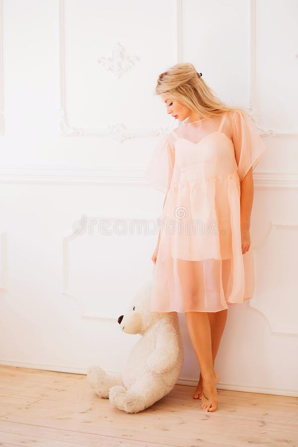 Full length portrait of happy beautiful woman in pink dress posing with a white soft toy white Teddy bear on hand in studio stock photo