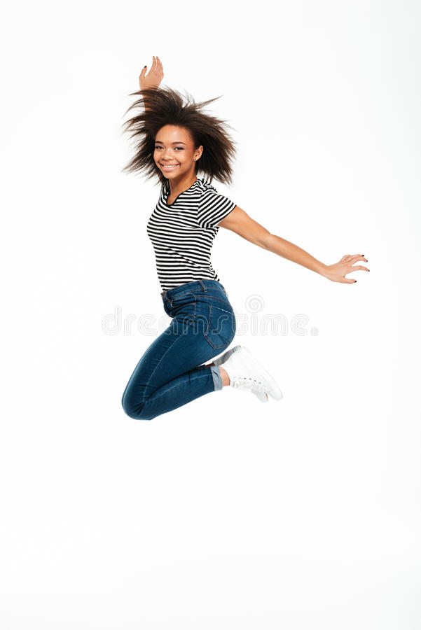 Full length portrait of a happy carefree african girl jumping royalty free stock photos
