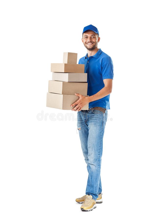 Full length portrait of happy delivery man holding stack of card. Board boxes isolated on white background stock image