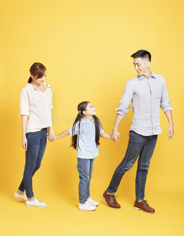 portrait of happy family walking over yellow background royalty free stock photos