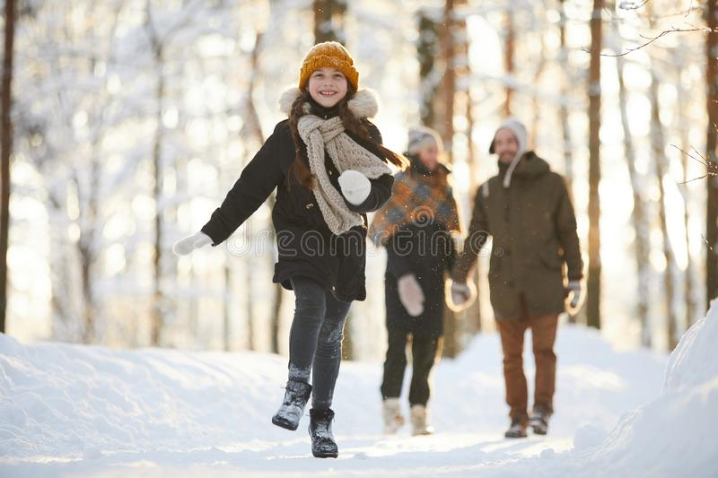 Happy Girl Running in Winter Forest. Full length portrait of happy little girl running towards camera in winter forest while enjoying walk with family, copy stock image