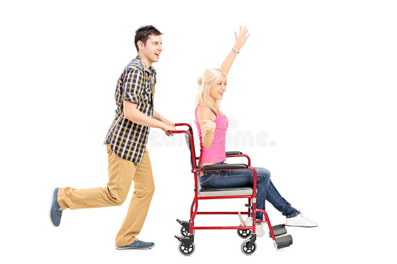 Full length portrait of a happy male pushing a female in wheelchair royalty free stock image