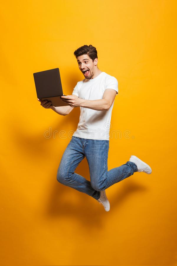 Full length portrait of happy man with brown hair jumping and ho. Lding black laptop isolated over yellow background stock image
