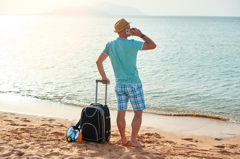 Full length portrait of happy man with suitcase and mobile phone standing on beach freelancer on a sunny day on vacation.  stock images