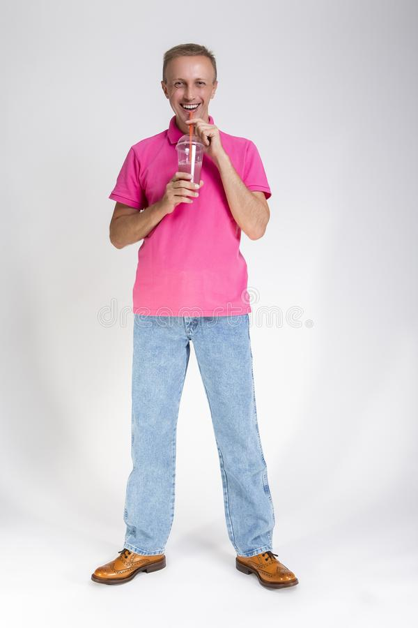 Full Length Portrait of Happy Smiling Caucasan Blond Man Holding Cup With Smoothie. Drinking Through Straw stock photo