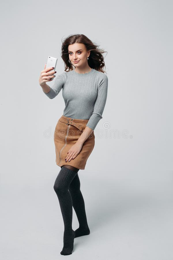 Young alluring girl doing photos. Full length portrait of happy stylish woman with charming smile in fashion sweater and brown skirt. She is standing and taking royalty free stock photo