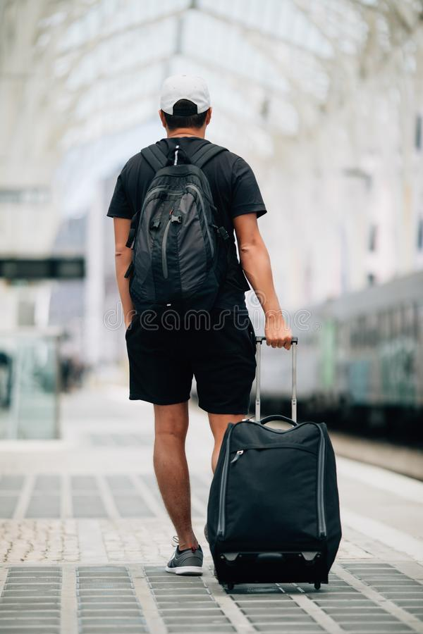Full length portrait of a happy young man walking with suitcase at train station. Travel concept stock photos