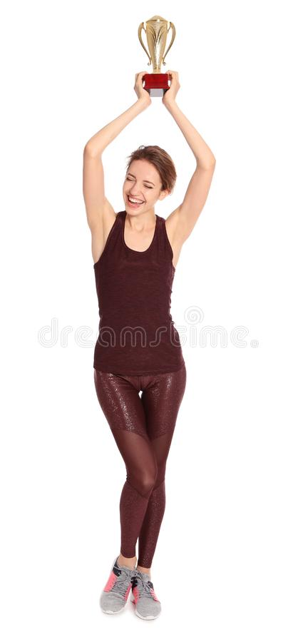 Full length portrait of happy young sportswoman with gold trophy cup on white stock photography