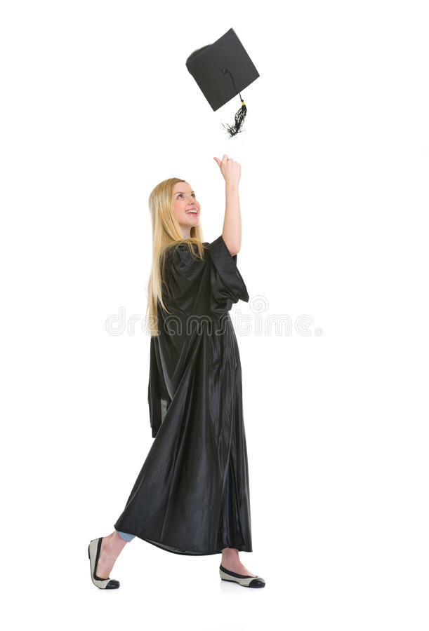 Happy young woman in graduation gown throwing cap. Full length portrait of happy young woman in graduation gown throwing cap up stock images
