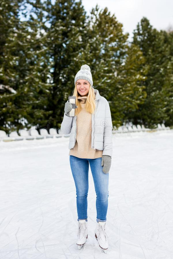Full length portrait of happy young woman ice skating and drinking coffee at outdoor rink. Full length portrait of happy young beautiful woman ice skating and royalty free stock images
