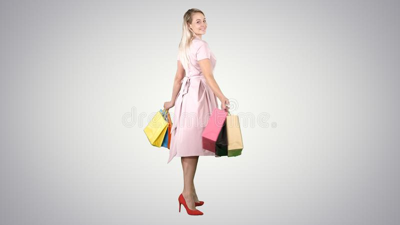 Happy young woman making a turn with shopping bags in her hands Looking at camera on gradient background. stock photos