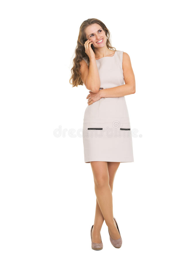 Full length portrait of happy young woman talking cell phone stock photo