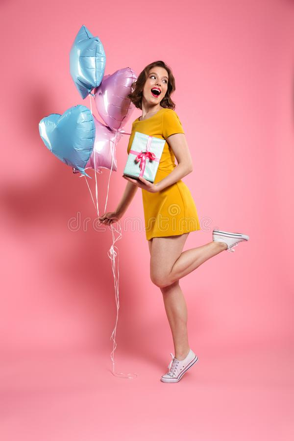 Full length portrait of happy young woman in yellow dress holding gift box and colorful balloons, looking aside stock image