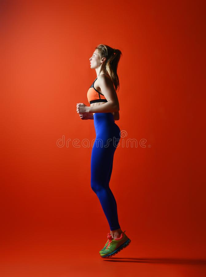Woman runner in silhouette on red background. Dynamic movement. Side view royalty free stock images
