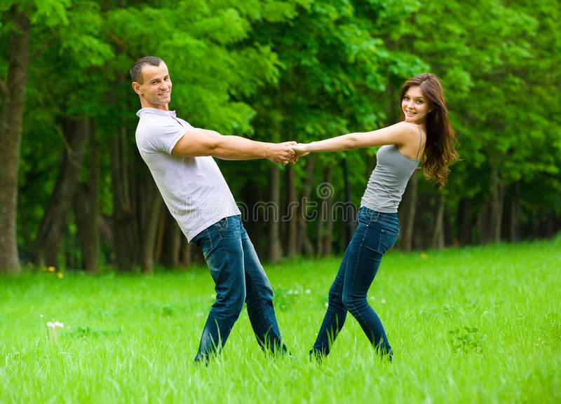 Full-length portrait of joining hands couple. In park. Concept of love and relations stock photo