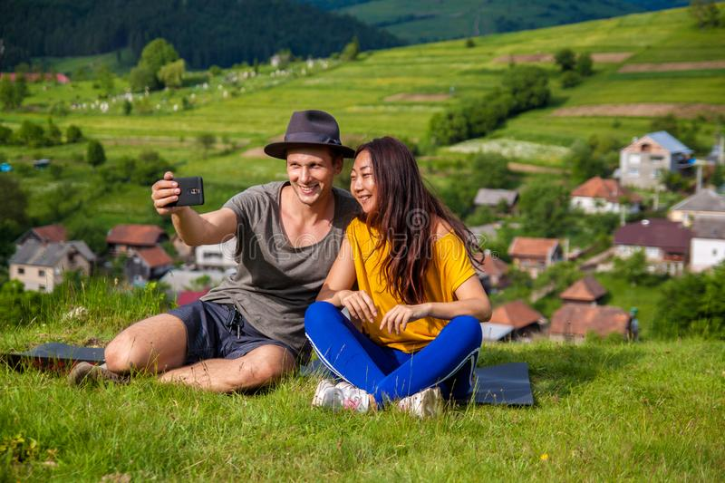 Portrait of joyful girl and boy sitting on the mountain and making selfie. stock images