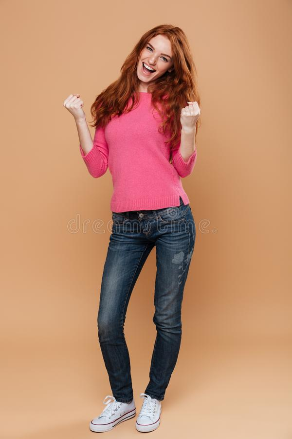 Full length portrait of a joyful young redhead girl celebrating. Over beige background stock photo