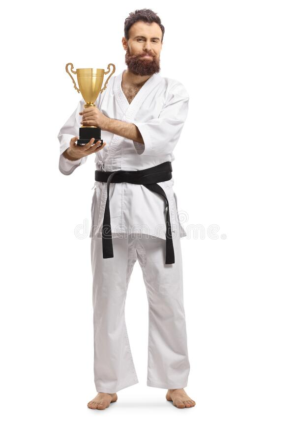 Full length portrait of a karate champion in kimono with a trophy cup royalty free stock images