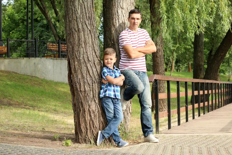 Full-length portrait of little boy and his father outdoors stock images