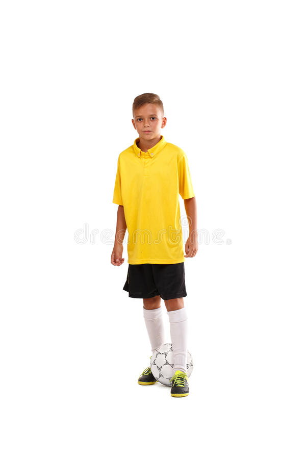 Full-length portrait of a little footballer in a yellow T-shirt, black shorts isolated on a white background. stock images