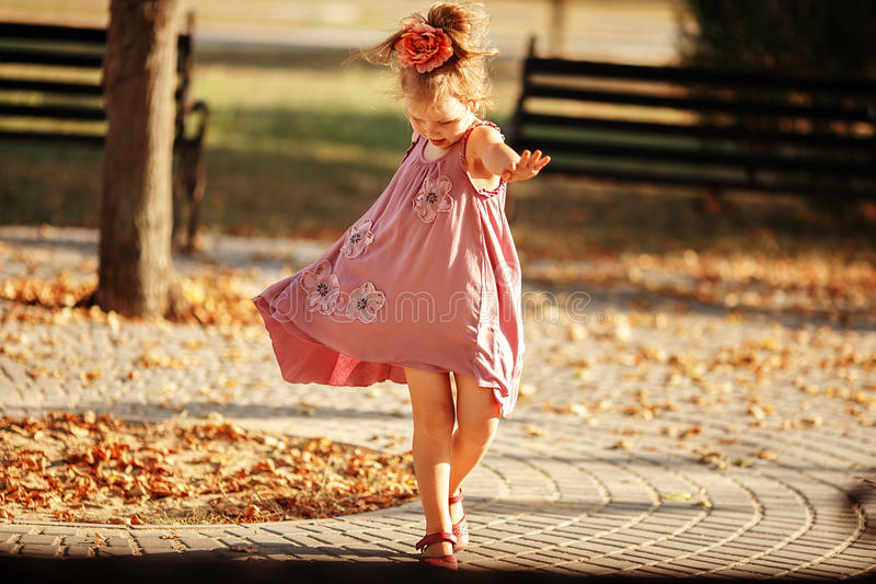 Full length portrait of a little girl dancing in the park a warm. Autumn evening. In move stock photo