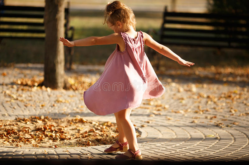 Full length portrait of a little girl dancing in the park a warm. Autumn evening. In move. Back view stock photos