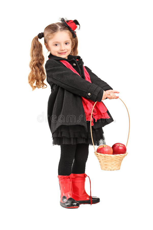 Full Length Portrait Of A Little Girl Holding A Basket With Appl Stock Photo