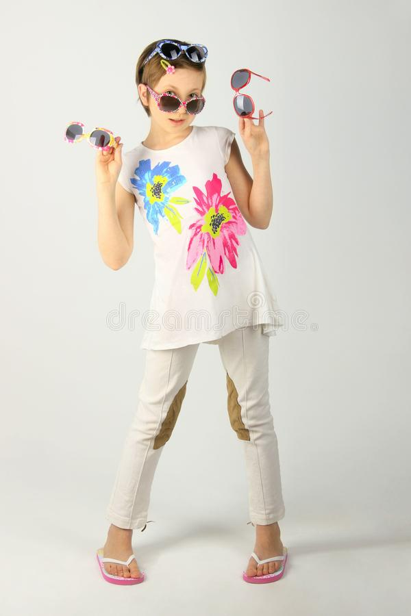 Adorable Girl Wearing sunglasses.Girl Wearing White Clothes And Colored Sunglasses. stock photography