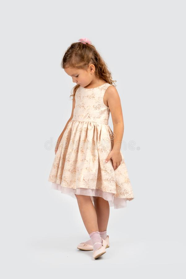 Full length portrait of a little smiling girl wearing beautiful beige elegant dress. stock photos