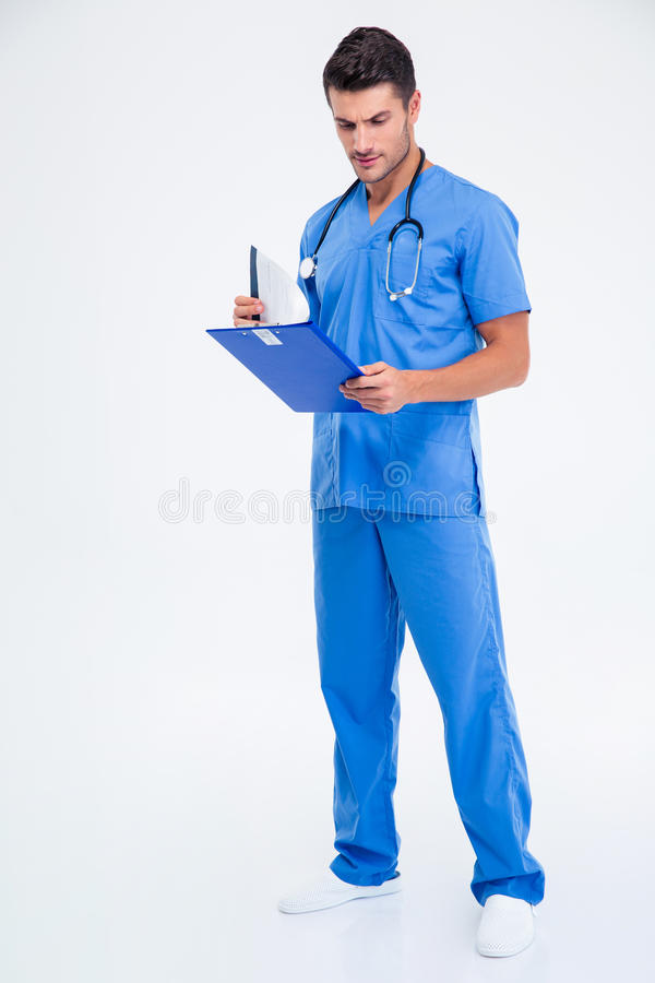 Full length portrait of a male doctor reading clipboard stock photography