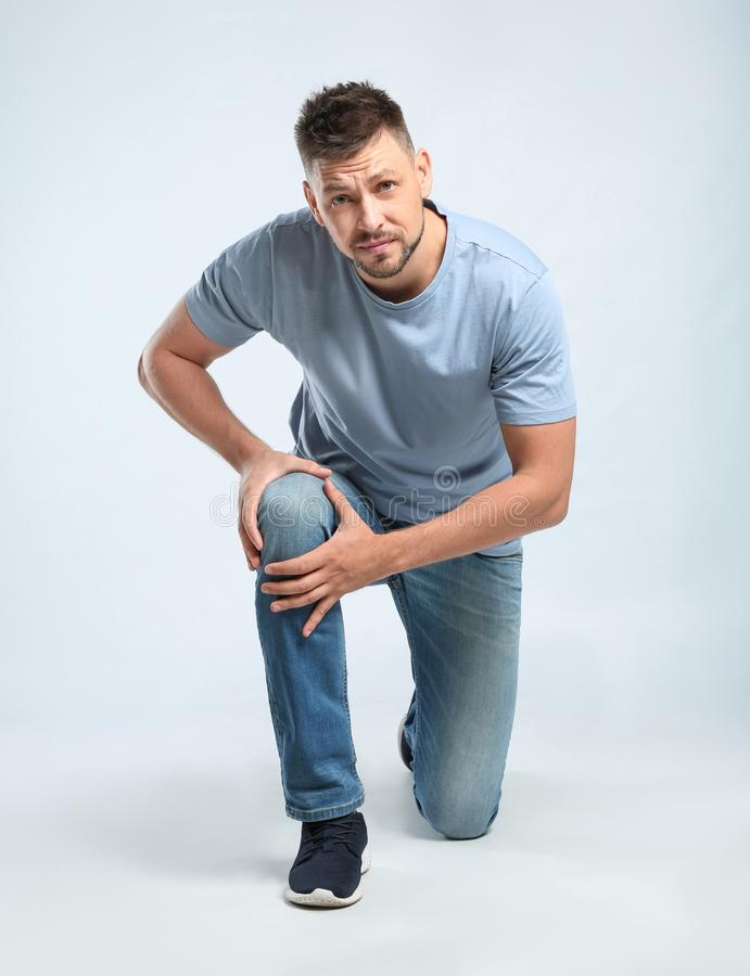 Full length portrait of man having knee problems on grey royalty free stock photos