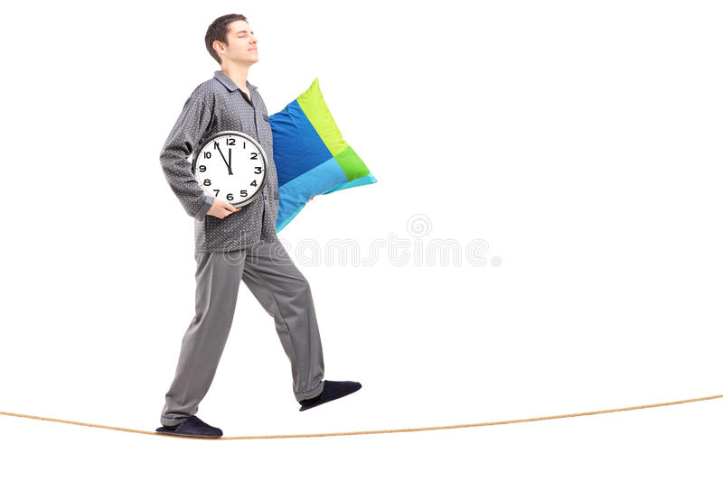 Full length portrait of a man with pillow and clock sleepwalking