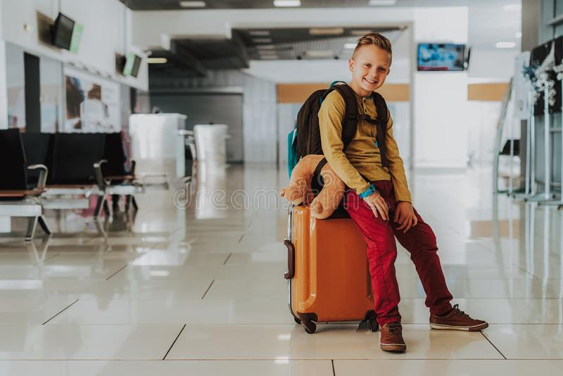 Jolly kid is waiting for flight at airport. Full length portrait of merry boy sitting on suitcase in lobby. He is carrying luggage for vacation. Copy space in royalty free stock photo