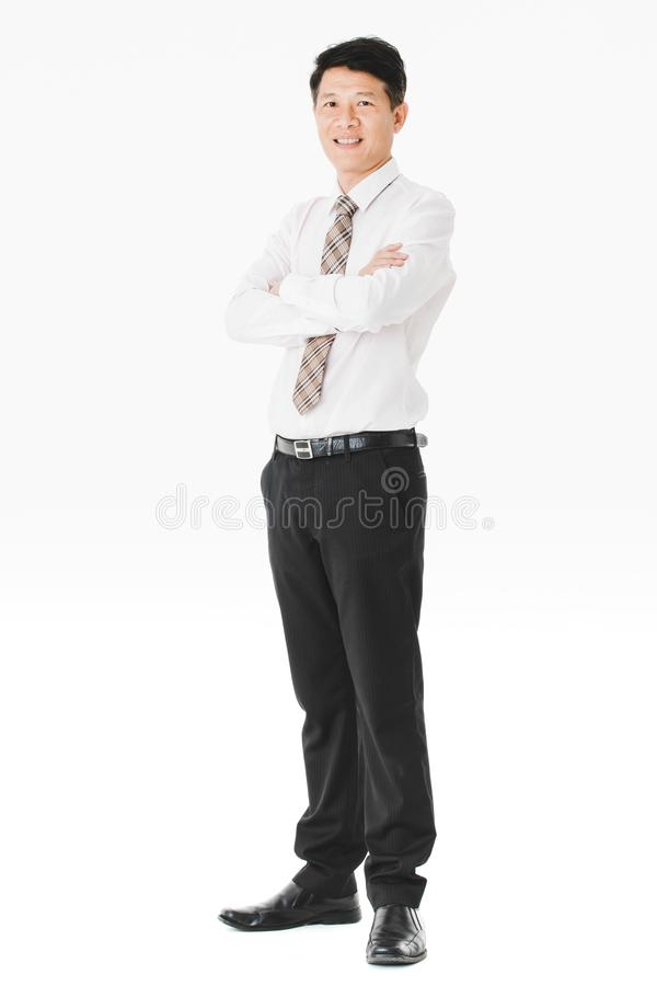 Asian business man isolated white. Full length portrait of middle aged, handsome, Asian, businessman, in white shirt, striped tie.black pants and shoes, holding royalty free stock image