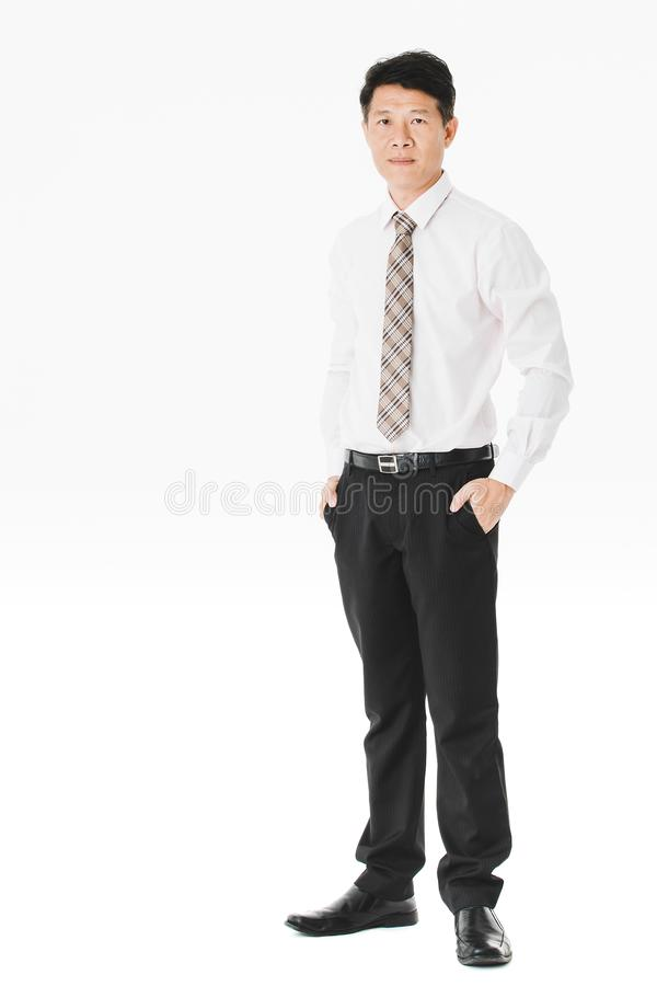 Asian business man isolated white. Full length portrait of middle aged, handsome, Asian, businessman, in white shirt, striped tie.black pants and shoes, posing stock images