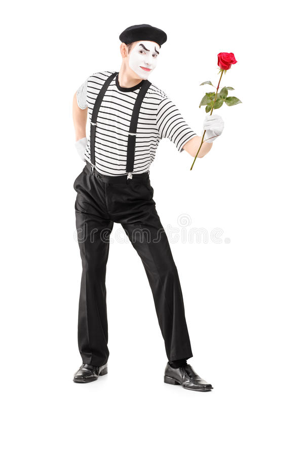 Full length portrait of a mime asrtist giving a rose flower stock images