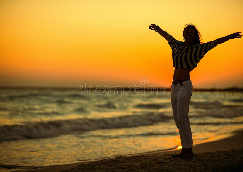 Modern woman on beach at sunset rejoicing. Full length portrait of modern woman on the beach at sunset rejoicing. Real freedom is only in our head! Nothing can stock images