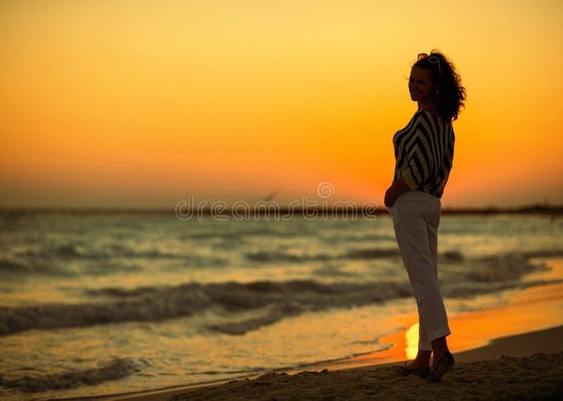 Full length portrait of modern woman on seashore in evening stock photos