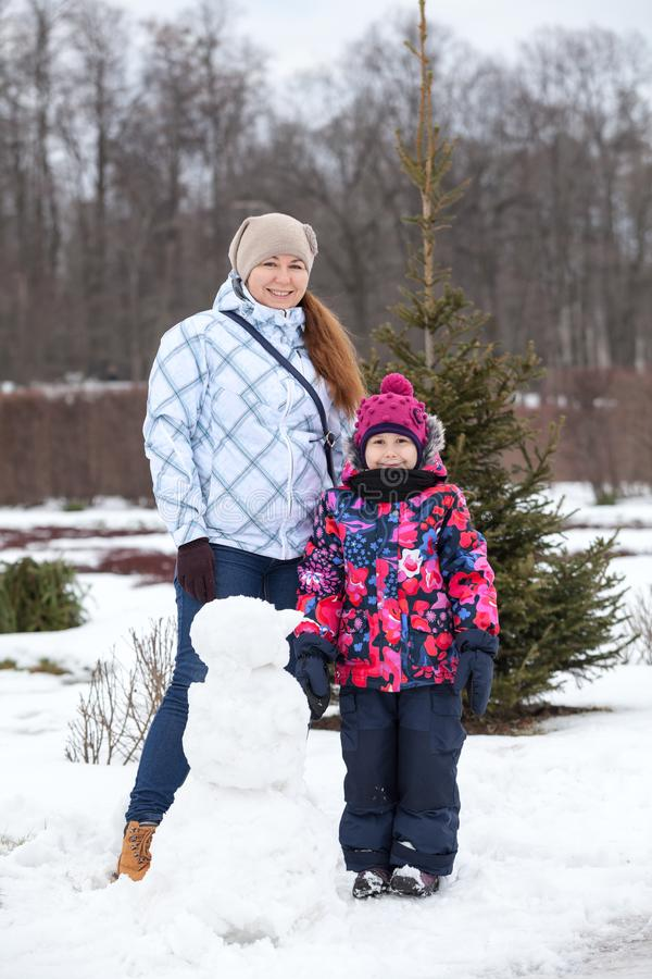 Full length portrait of mother, child and snowman, people play with snow in winter park royalty free stock image