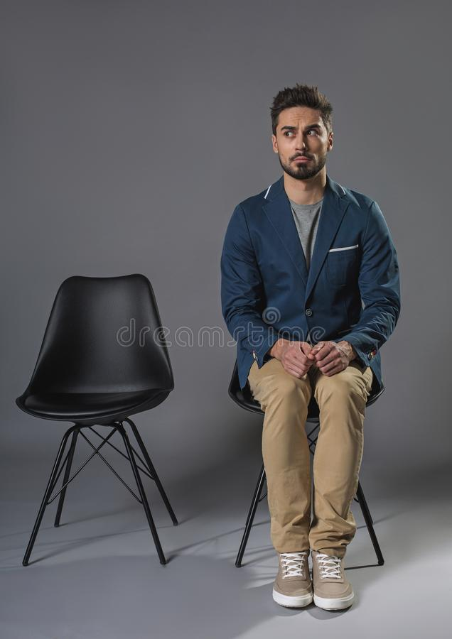 Young excited man sitting on the chair. Full length portrait of nervous male is open-eyed. He is waiting for his turn on chair. Copy space in left e royalty free stock photo