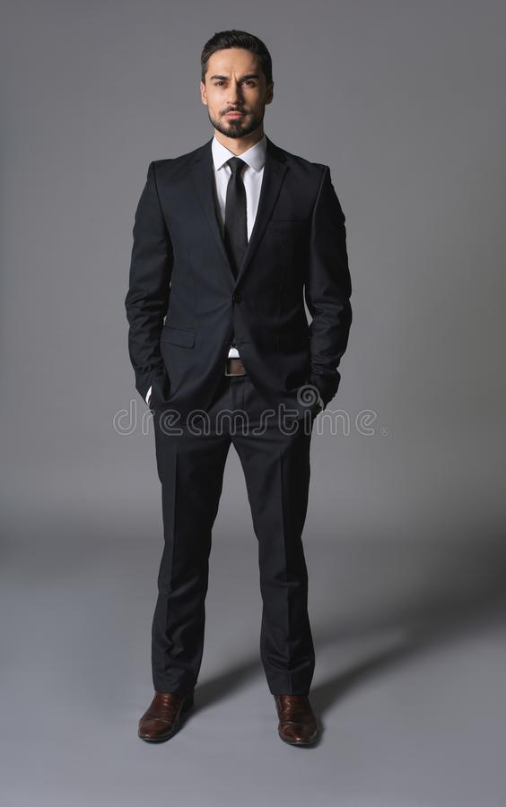 Young serious successful businessman standing with hands in pockets royalty free stock photos