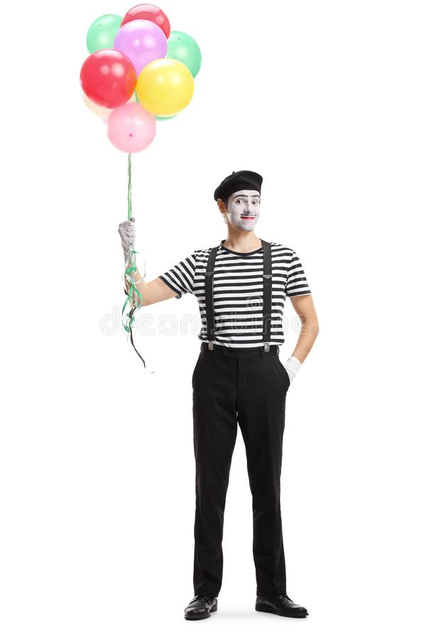 Pantomime man standing with a bunch of balloons stock images