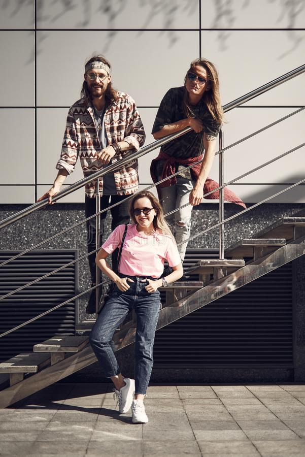 Cheerful friends locating at street. Full length portrait of pleased males with long hair wearing glasses and situating on ladder outdoor. Glad women standing royalty free stock photos