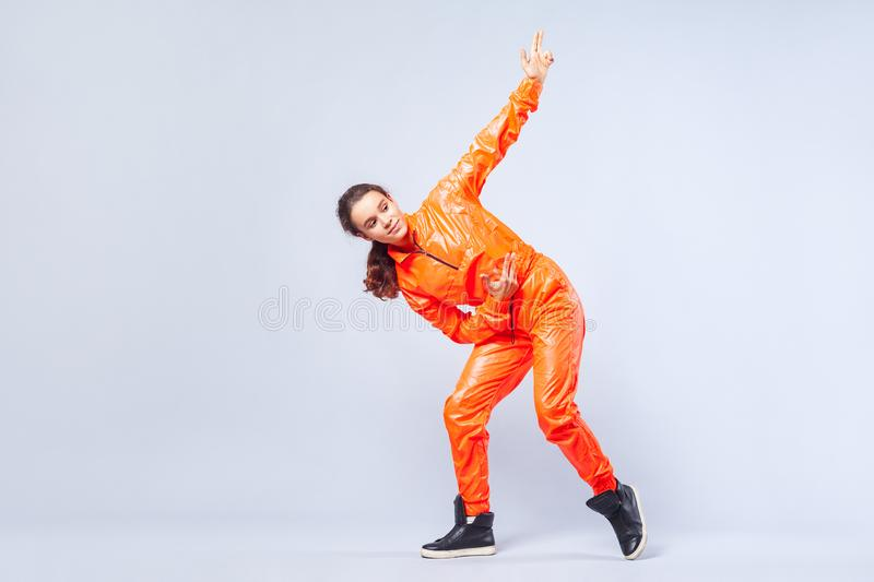 Full length portrait of positive energetic teen girl dancing hip-hop and pointing up with finger pistol, white background stock photos